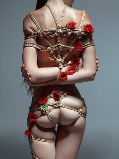 woman with hands tied using shibari rope bondage
